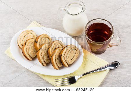 Swiss Roll Cake In Glass Dish On Towel, Jug Milk