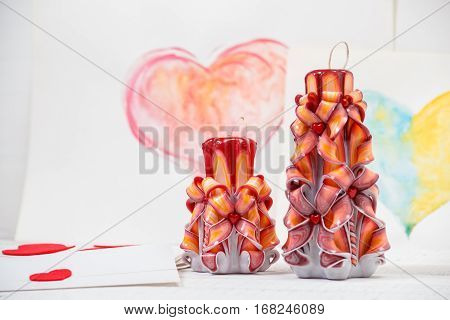 St. Valentine's Day: two carved candles of orange color against the background of pink heart. Symbol.