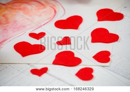 St. Valentine's Day: contrast of red and white color. Symbol of pure love. Red heart from felt. Creativity by the hands.