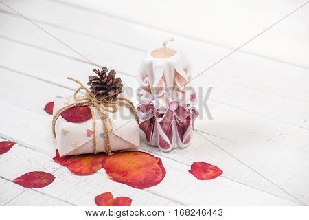 St. Valentine's Day: one carved candle of lilac color, gift and petals of roses. It is made with own hands.