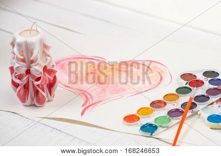 St. Valentine's Day: big pink heart, carved candle and palette of paints. Simbol