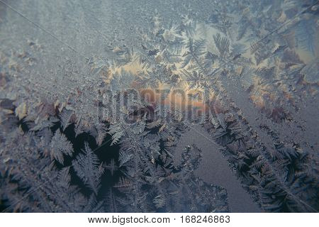 hoarfrost at a window against the background of decline dawn winter