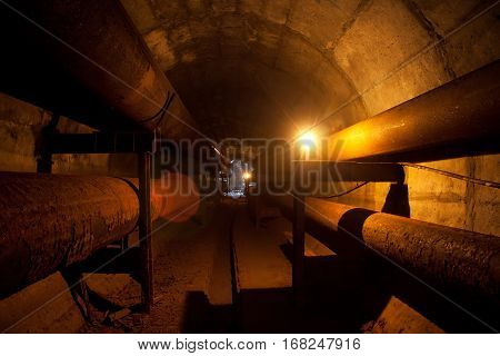 Round underground tunnel of heating duct with rusty tubes illuminated by candles