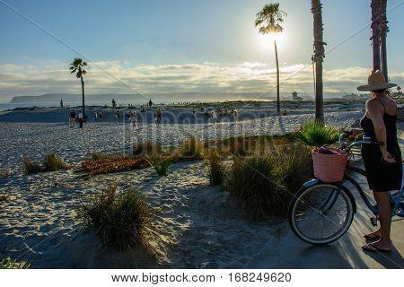 San Diego, California, USA - July 3, 2015: cyclist watches the sunset on the beach of Coronado in San Diego