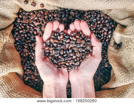 Coffee concept. Hands in sac with roasted coffee beans. Black coffee