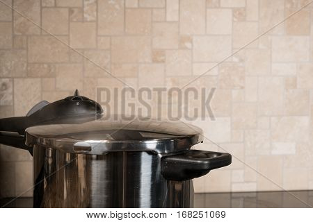 Stainless steel pressure cooker letting off steam on a modern induction cooking hob with glass top
