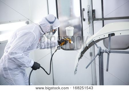 automobile repairman painter in protective workwear and respirator painting car body elements in paint chamber