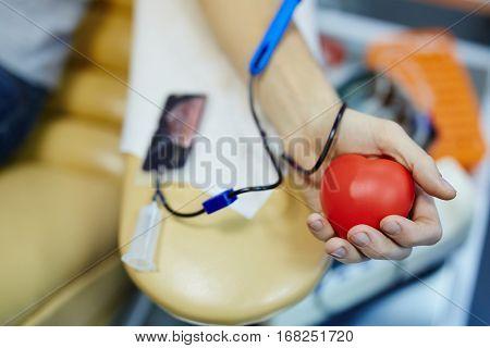 Male hand holding red rubber flexor
