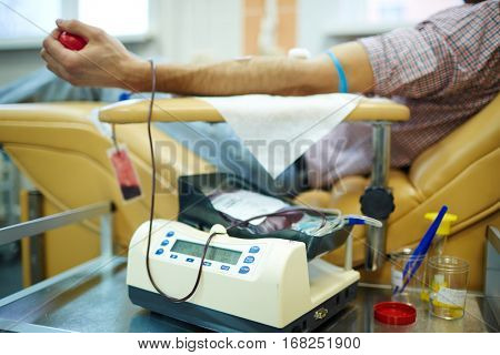 Equipment for donating blood and human lying in armchair on background