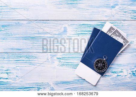 Compass On Passports With Boarding Pass And Dollar Banknotes On Blue Wooden Background