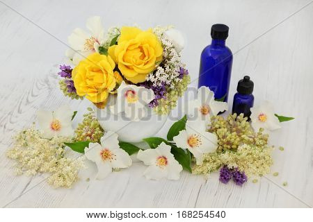Healing flowers and herbs with rose, valerian, elderflower, orange blossom, lavender and angelica seed heads with essential oil bottles and mortar with pestle.