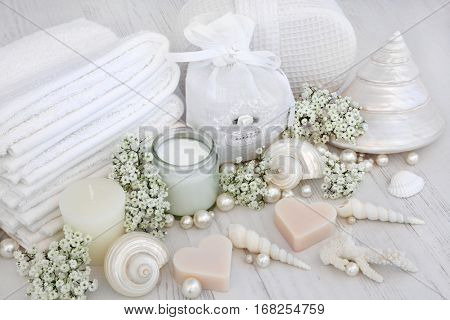 Luxury spa products with white face towels, sponge, cream and flowers with shells and pearls over distressed wood background.