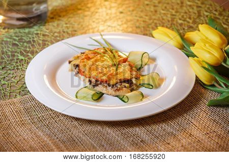 Fried Turkey steaks with cheese and mushrooms on a plate and on a burlap. Turkey meat garnish with green parsley and fried mushrooms. Old wooden background with free place for text