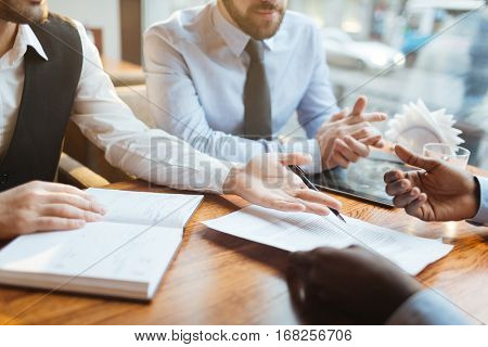 Close-up view of confident bearded businessmen in suits sitting at wooden table near window and discussing new contract terms before signing it.