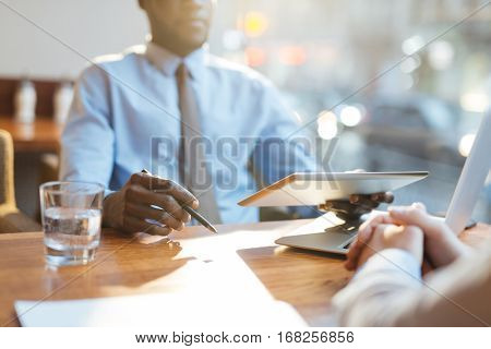 Close-up view of African-American businessman holding tablet and discussing company development with his partner in cafe as sun illuminating table brightly.