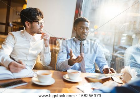 Confident African-American manager offering new company strategies to his intent bearded partner in glasses while having tea break in cafe.