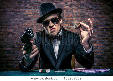Cool mafia gangster with a gun sitting at a game table in a casino. Gambling, playing cards and roulette.