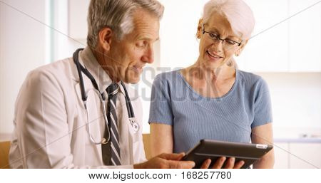 Senior Doctor Talking With Elderly Woman Patient In The Office With Tablet
