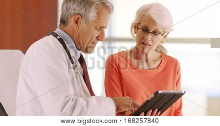 Friendly Senior Doctor Talking With Elderly Woman Patient In The Office