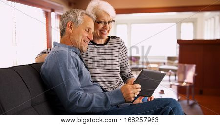 Senior Couple Sitting On Couch Watching Videos On Tablet