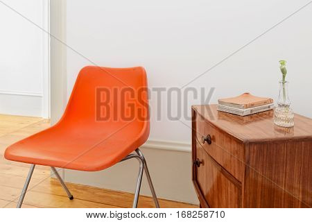 A Retro Nightstand With Books And Orange Chair
