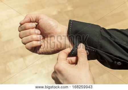 Buttoning the sleeve of a black shirt