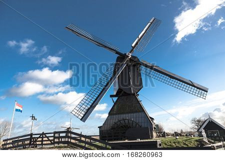 Old windmill with the Netherlands flag. White clouds on a blue sky, the wind is blowing