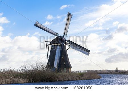 Traditional dutch windmill near the canal. Netherlands. Old windmill stands on the banks of the canal, and water pumps. White clouds on a blue sky, the wind is blowing.