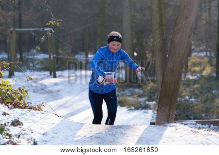 OLDENZAAL NETHERLANDS - JANUARY 22 2017: Unknown female jogger stumbles up a hill during a cross run in a snowy white forest