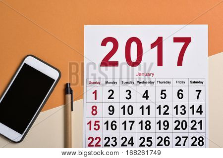 high-angle shot of a 2017 calendar, a smartphone and a pen on a desk