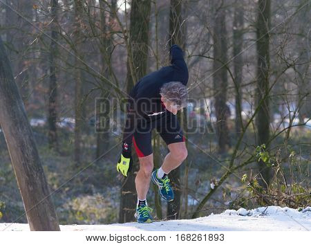 OLDENZAAL NETHERLANDS - JANUARY 22 2017: Unknown athlete stumbles up a hill during a cross run in a snow white landscape