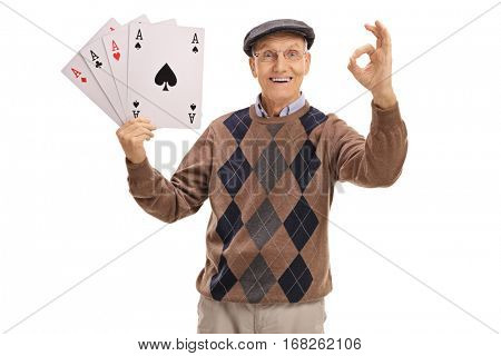 Cheerful senior holding four aces and making an ok sign isolated on white background