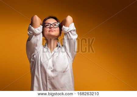 Young pretty beautiful emotional girl in glasses posing on a yellow background. Joyful emotions of girl good impression of women. The girl dreaming and from this it becomes fun. Gentle girl.