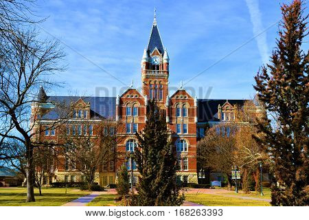 Old historic brick building with a clock tower surrounded by manicured landscaping taken Friends University in Wichita, KS