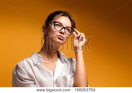 Young pretty beautiful emotional girl in glasses posing on a yellow background Gentle dreaming young girl thought woman. Thoughtful girl. Thoughtful woman. The girl adjusts glasses woman.