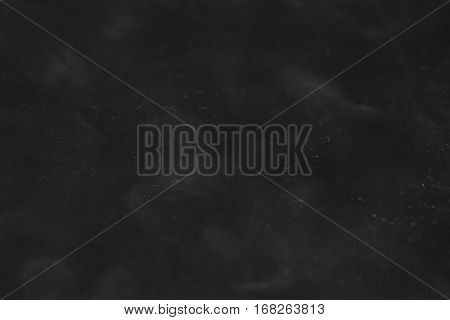 The texture of dirty scratched plastic. Abstract rectangular dark background with light blur.