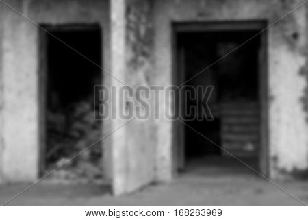 Blurred black and white background. The entrance of an abandoned house. A pile of debris inside the building.