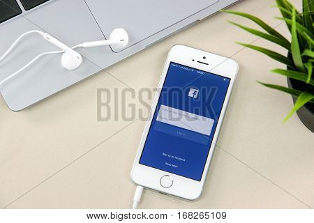 Krynica Poland - February 02 2017: Facebook app on iPhone SE close to a laptop. Facebook is one of the most popular social media service app on the world.