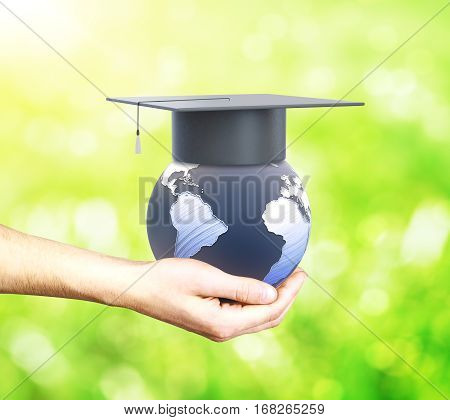 Hand holding globe with graduation cap on green background. Education abroad concept. 3D Rendering.