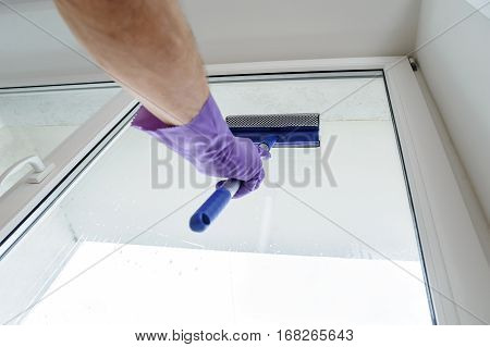 A man cleans the windows in the house. The hand in rubber glove is holding scraper for cleaning windows.