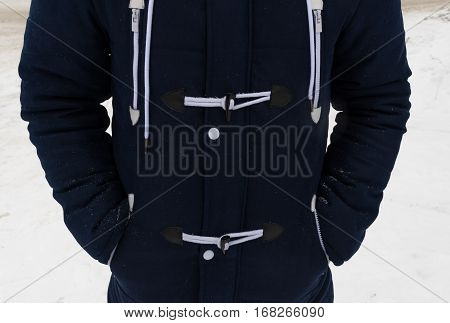 Detail of a man's torso in a fashionable winter jacket. Blue parka with laces and rivets. Close-up horizontal photo.
