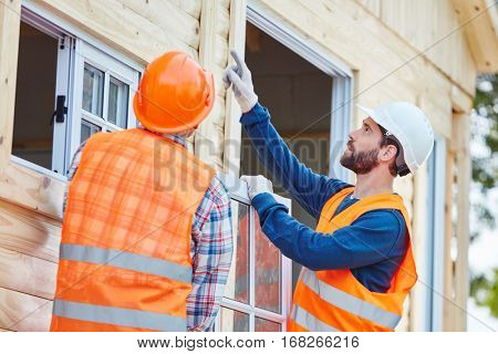 Two window fitter cooperating and installing window for new house