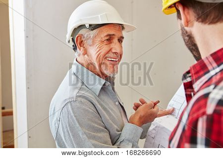 Senior citizen as craftsman with experience cooperating with foreman