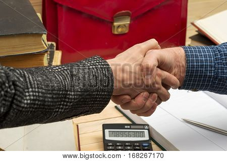 Business concept. Business partners handshaking after signing contract. Pertnership. On a wooden table books documents calculator red briefcase