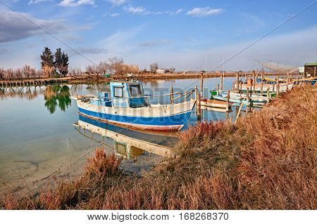 Ravenna, Emilia Romagna, Italy: landscape of the wetland in the nature reserve Po Delta Park with small fishing boats in the canal of the lagoon