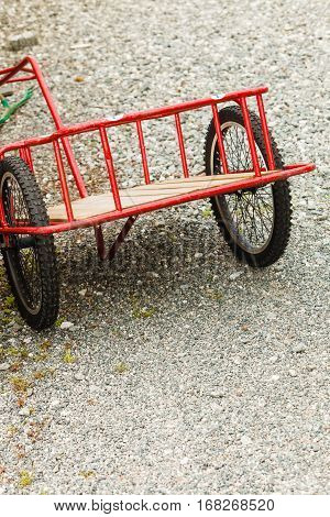 Closeup of red gardening trolley with big wheels standing outside on paved surface