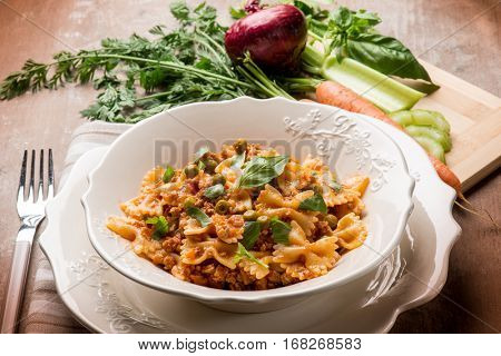 butterfly pasta with ragout sauce and green peas