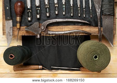 Leather craft tools on a wooden background. Craftmans work desk . Piece of hide and working handmade tools on a work table. Top view