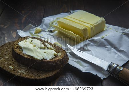 Sandwich with butter. Black rye bread, butter parchment, a kitchen knife on a dark wooden fone.Selektivny focus. Low-key style.