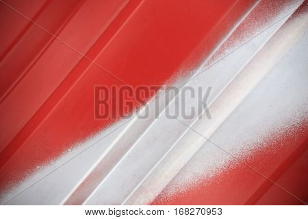 Close up of white painted line on red metal background. Red steel container wall with white line closeup. Red ribbed transportation container wall.